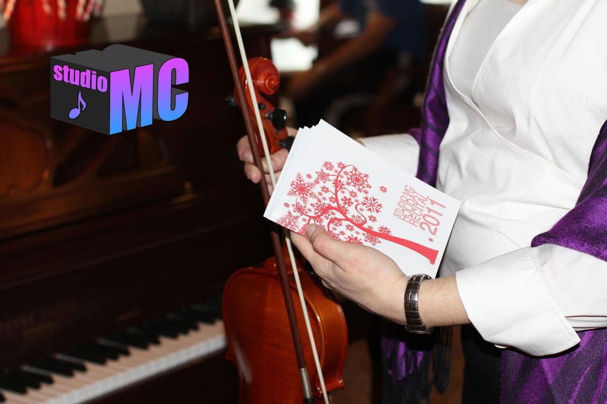 Mc holding her violin near a piano